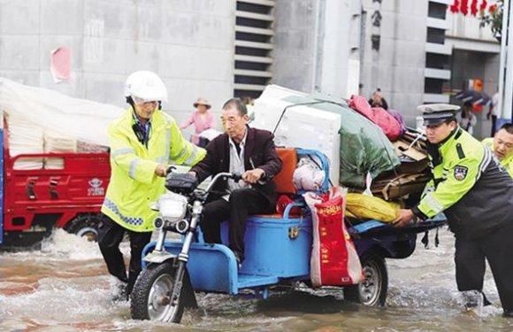 暴雨突袭 云南宣威城民警背老人过马路
